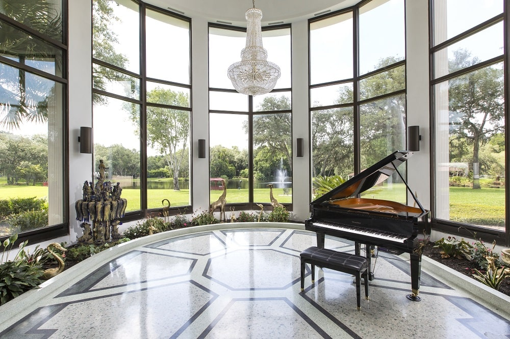 The mansion also has a music room that has a black grand piano. This is surrounded by tall curved glass walls and topped with a chandelier. Image courtesy of Toptenrealestatedeals.com.