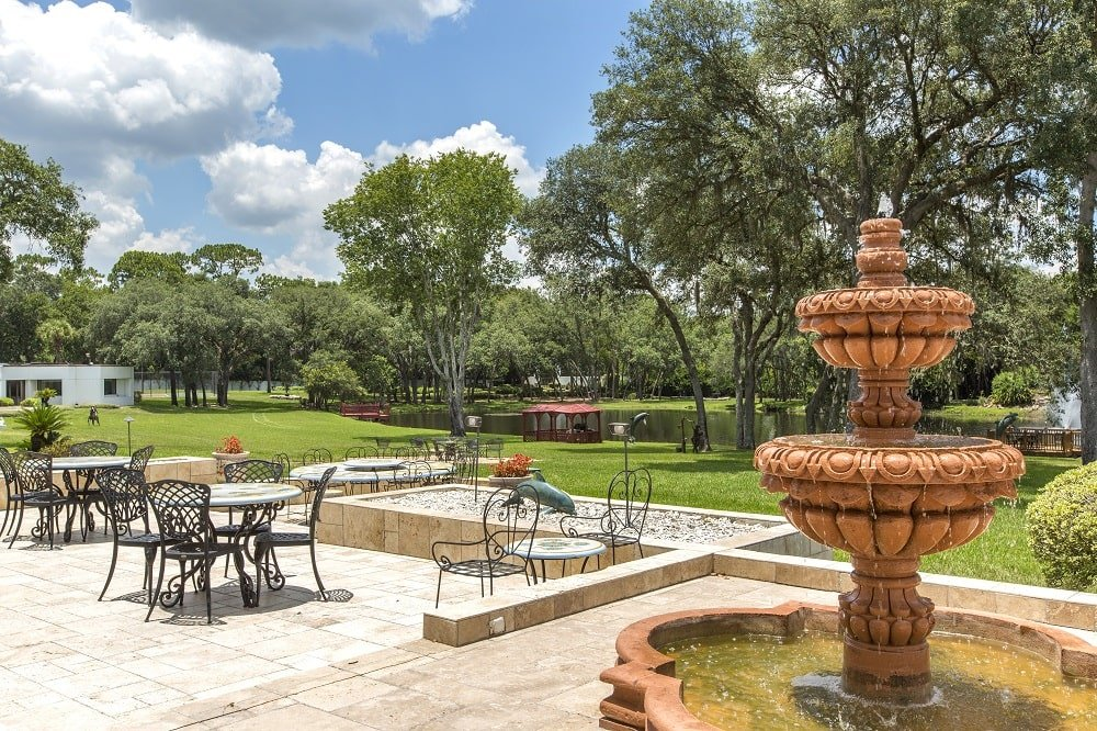 The outdoor patio is fitted with outdoor dining sets that stand out against the beige stone floor. On the side of this is a brown stone fountain. Image courtesy of Toptenrealestatedeals.com.