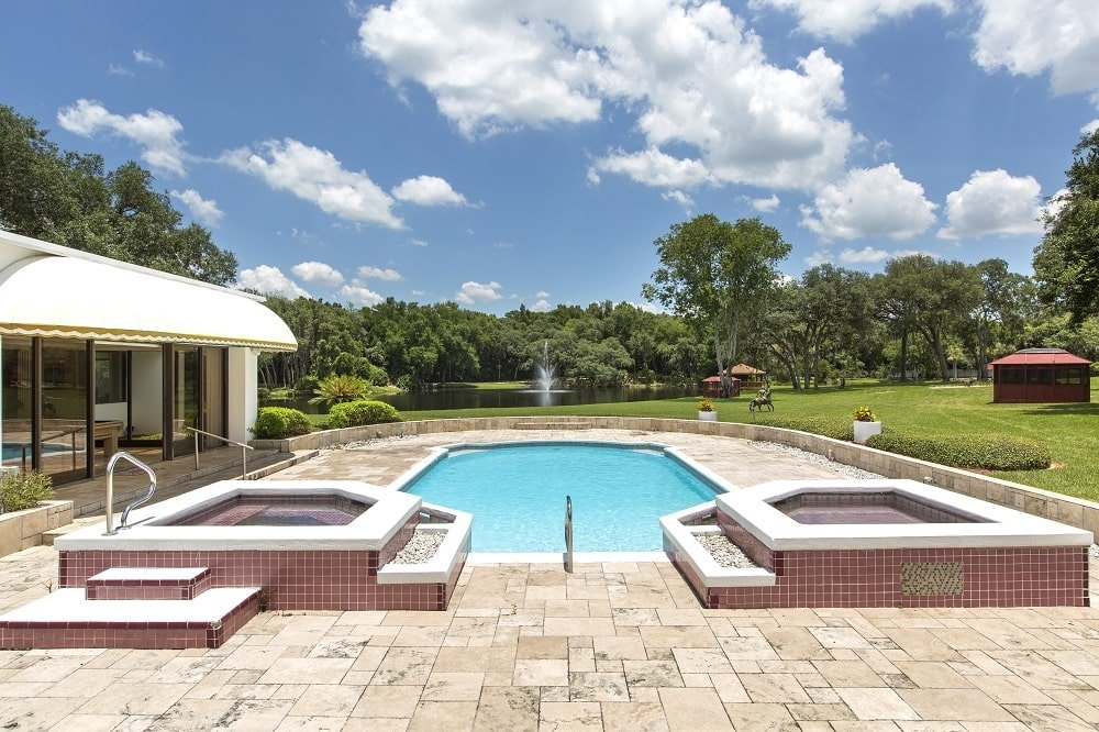 This is a view of the swimming pool of the mansion that is surrounded by beige stone walkways. These are then complemented by the surrounding landscape that has large grass lawns and tall trees in the distance. Image courtesy of Toptenrealestatedeals.com.