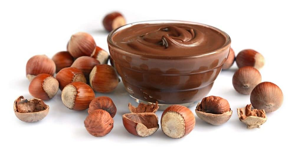 A bowl of hazelnut butter surrounded by hazelnuts.