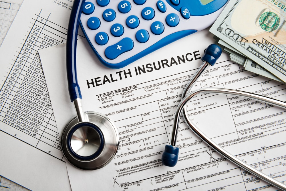 Health insurance papers, dollar bills, a stethoscope, and a calculator.