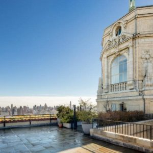 This is a look at one of four apartments of the penthouse from the vantage of the large terrace adorned with potted plants and has a view of the city. Image courtesy of Toptenrealestatedeals.com.
