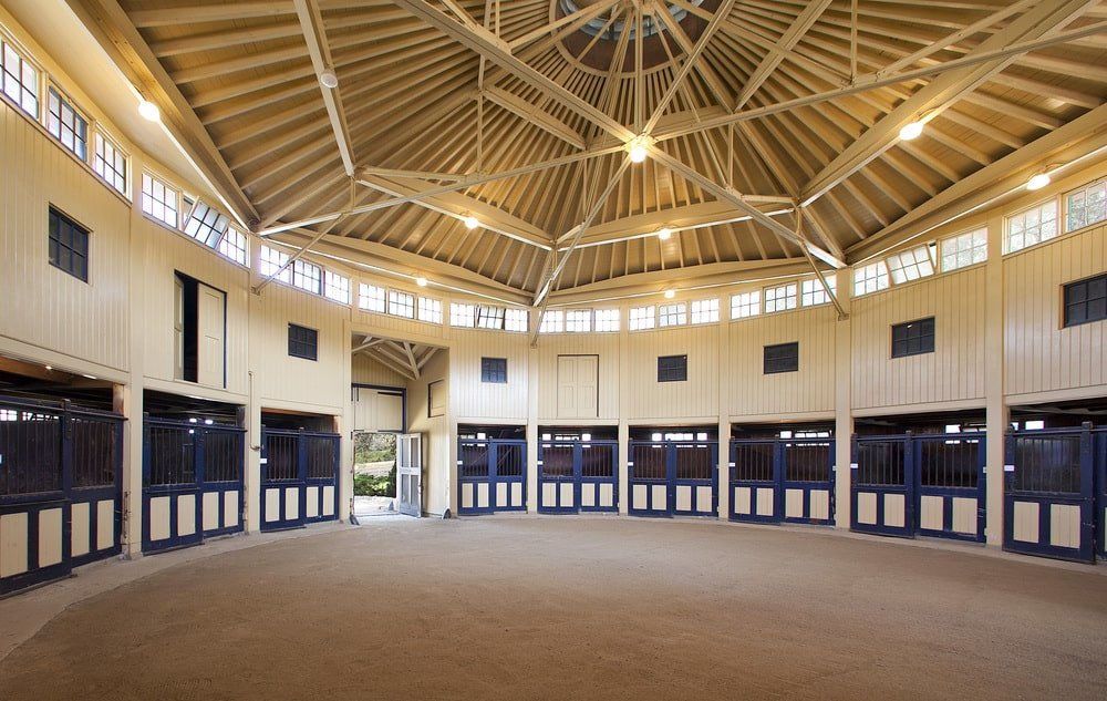 This is the interior of the barn with stables for multiple horses. This has a tall cove ceiling with exposed beams and spotlights. Image courtesy of Toptenrealestatedeals.com.