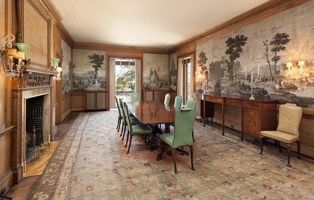This formal dining room has a large wooden dining table surrounded by green upholstered chairs. These are then complemented by the surrounding wooden wainscoting and the mural at the upper walls. Image courtesy of Toptenrealestatedeals.com.