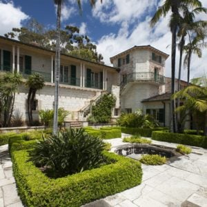 This is a front view of the house from the vantage of the courtyard. You can see here the bright exterior walls of the house adorned by the landscape of the courtyard that has tall tropical trees and well-maintained shrubs. Image courtesy of Toptenrealestatedeals.com.