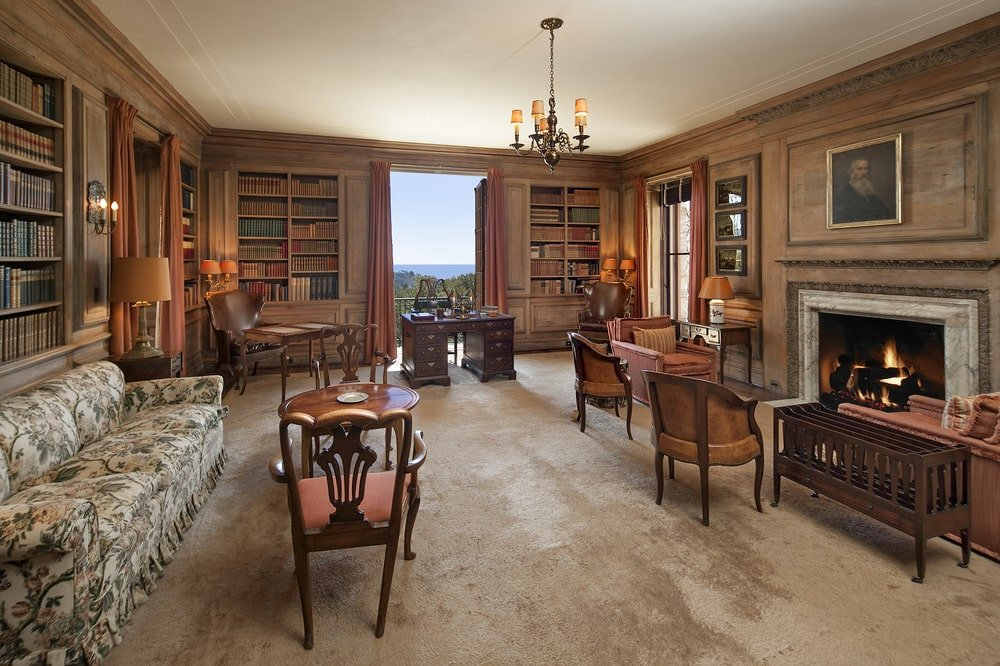 This is the library with built-in wooden bookshelves embedded into the wood-paneled walls. There is also a large fireplace across from the armchairs. Image courtesy of Toptenrealestatedeals.com.