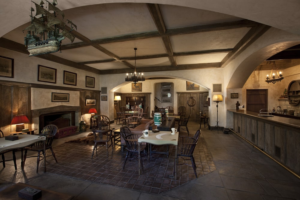 This is the European-style pub that can only be accessed with a hidden door. It has a fireplace that matches with the furniture and the accesnt of the ceiling that hangs a chandelier. Image courtesy of Toptenrealestatedeals.com.