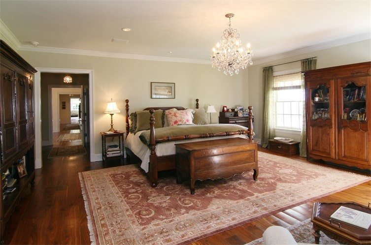 The primary bedroom has a wooden four-poster bed that matches the hardwood flooring topped by a colorful patterned area rug. Image courtesy of Toptenrealestatedeals.com.
