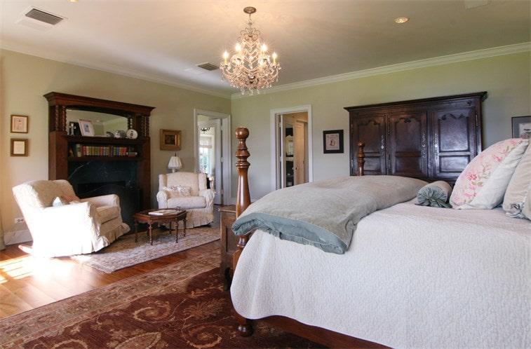 This other look of the bedroom shows the couple of beige armchairs across from the bed by the fireplace. Image courtesy of Toptenrealestatedeals.com.