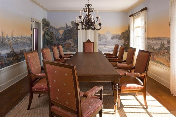 The formal dining room has upholstered dining chairs surrounding the large rectangular dining table. These are complemented by the surrounding mural on the walls. Image courtesy of Toptenrealestatedeals.com.