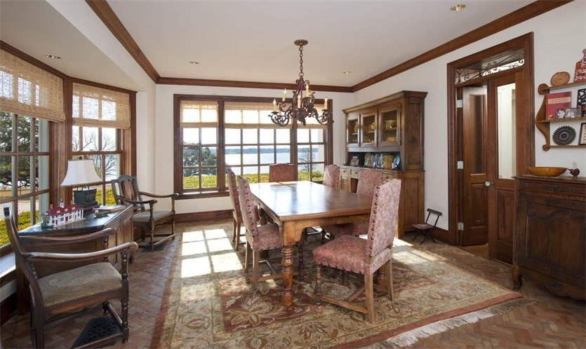 This other dining room has a dark wooden dining table under a small chandelier. This table matches the cabinet on the wall that stands out against the beige tones. Image courtesy of Toptenrealestatedeals.com.