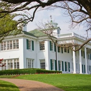 This is a look at the white mansion with large windows, bright white exterior walls and tall pillars. These stand out against the surrounding green landscape. Image courtesy of Toptenrealestatedeals.com.