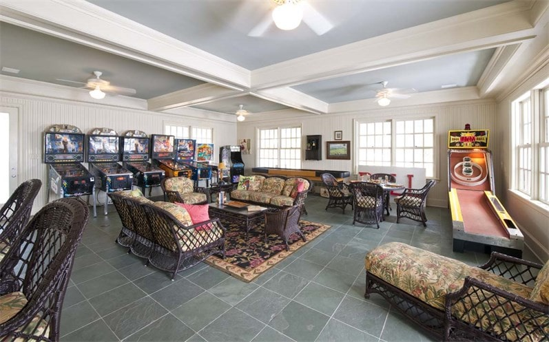 This is the game room with various comfortable woven wicker sofas and game machines under a large white ceiling with exposed beams. Image courtesy of Toptenrealestatedeals.com.