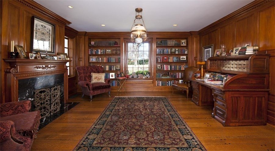 This is the office and library with consistent dark wooden tone to its walls, floor and the built-in bookshelves. These also match the desk and mantle of the fireplace. Image courtesy of Toptenrealestatedeals.com.