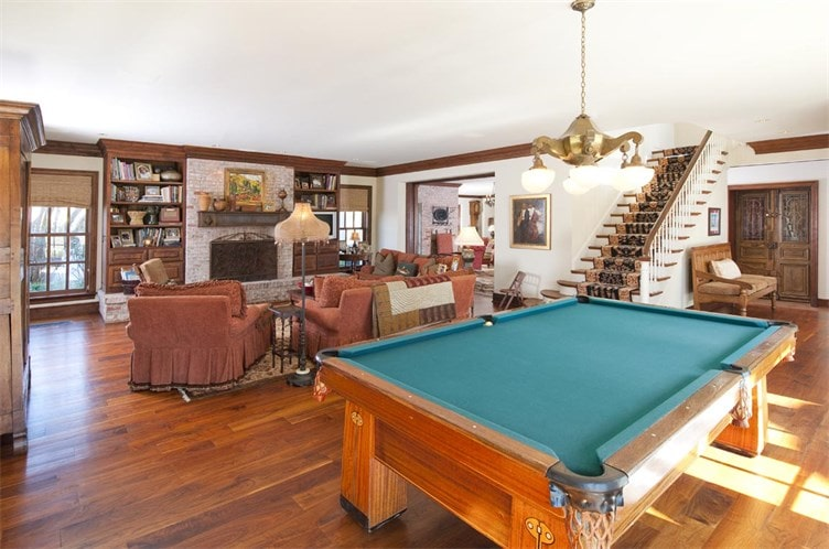 This other living room has comfortable sofas facing the stone fireplace on the far side. Behind the chairs is a large pool table topped with a chandelier. Image courtesy of Toptenrealestatedeals.com.