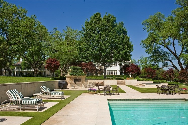 This is a close look at the poolside area with concrete walkways and various lawn chairs placed on grass lawns. On the far side you can see the pool house adorned with tall trees of the landscape. Image courtesy of Toptenrealestatedeals.com.