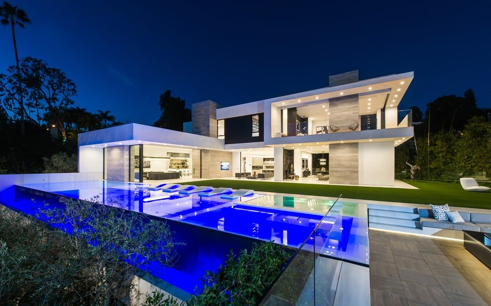 This is a look at the back of the house showcasing a modern pool with lighting complemented by the warm interior lights of the house escaping through the open walls and glass walls.
