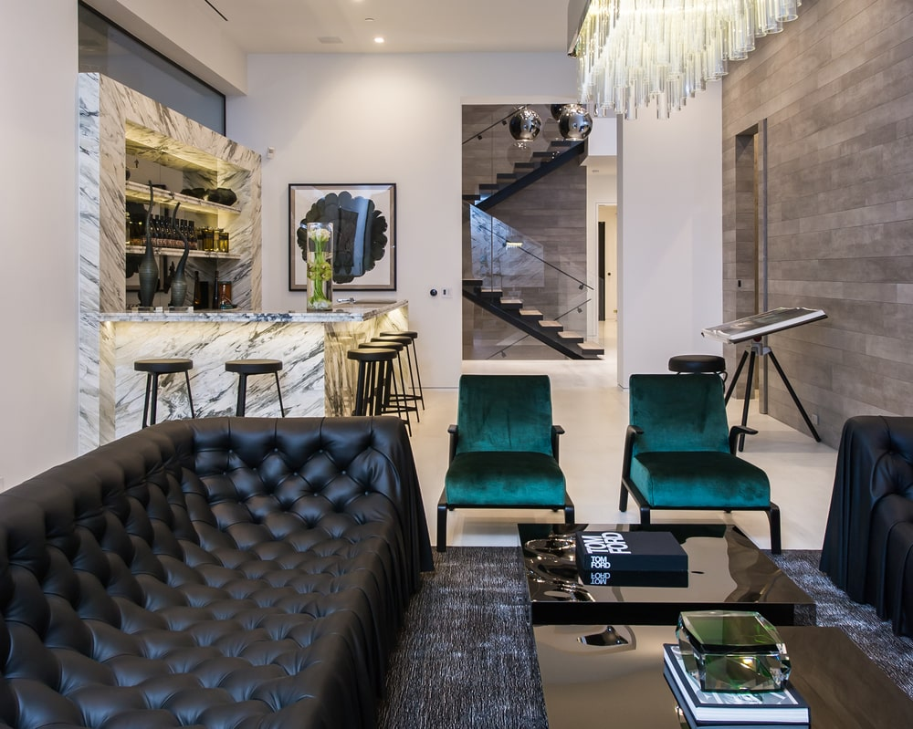 This is a look at the bar on the far corner with a white marble peninsula. On the side of this is a lounge area with a tufted black sofa to match the black coffee table and area rug. Image courtesy of Toptenrealestatedeals.com.