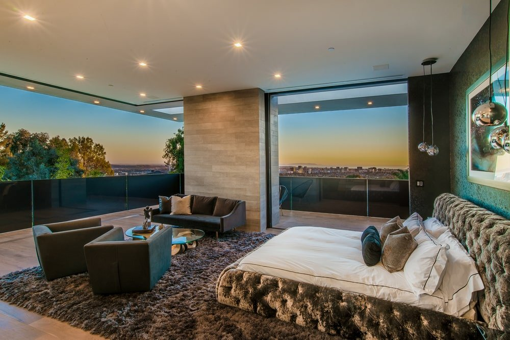 The primary bedroom f the house has a tufted bed frame with glass walls that offer a sweeping view of the city below. Image courtesy of Toptenrealestatedeals.com.
