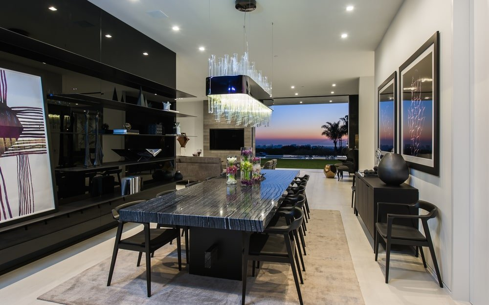 The formal dining room has a large dark-toned dining table surrounded by matching dark chairs that stand out against the light floor and ceiling with recessed lights. Image courtesy of Toptenrealestatedeals.com.
