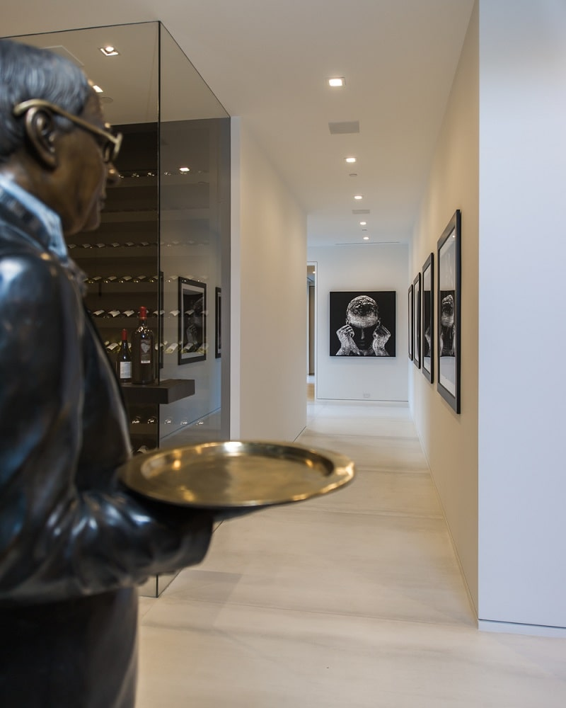 This is a look at the glass-enclosed wine cellar of the house. On the side of this is a hallway lined with wall-mounted artworks and a butler statue on the side. Image courtesy of Toptenrealestatedeals.com.