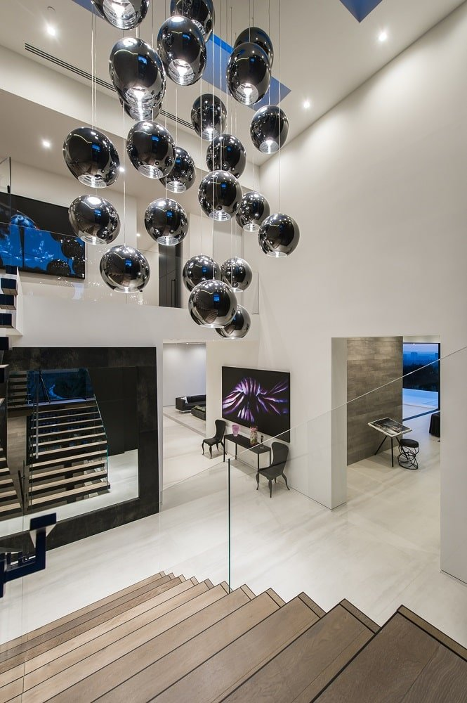 This is a look at the foyer from the vantage of the second-floor landing. You can see here the tall bright white ceiling that matches the walls to make the spherical decorative hanging artwork stand out. Image courtesy of Toptenrealestatedeals.com.