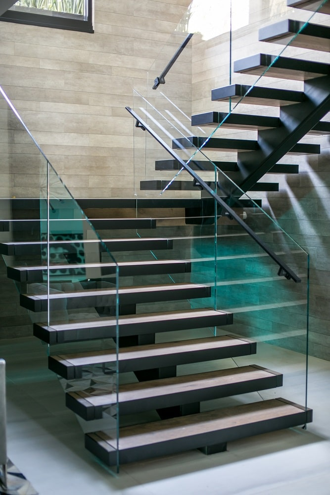This is a closer look at the modern staircase at the foyer that is bordered with glass for a unique look. Image courtesy of Toptenrealestatedeals.com.