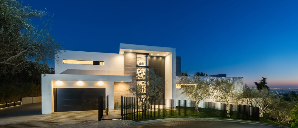 This is a look at the front of the house showing the bright white exterior walls complemented by the glass panels and dark brown garage door. Image courtesy of Toptenrealestatedeals.com.