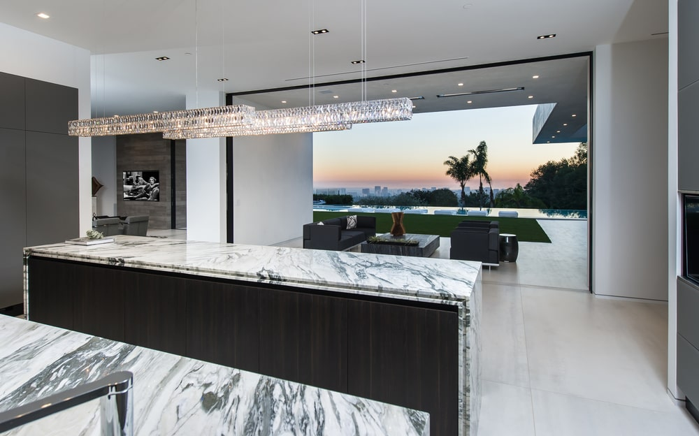This is the kitchen with a couple of dark wooden kitchen islands contrasted by the white marble countertops. Image courtesy of Toptenrealestatedeals.com.