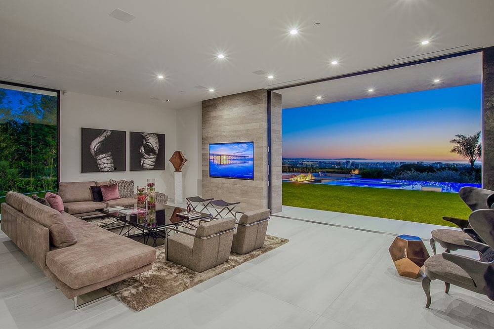 The living room has a modern set of sofa surrounding a coffee table across from a wall with an embedded TV. On the side of this is an open wall that leads to the backyard pool area. Image courtesy of Toptenrealestatedeals.com.