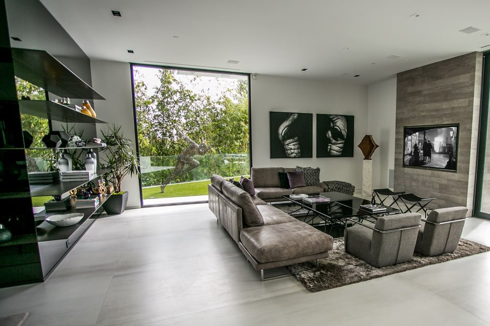 This other view of the living room shows a large glass wall and a black shelving at the back of the sofa that also serves as a divider. Image courtesy of Toptenrealestatedeals.com.
