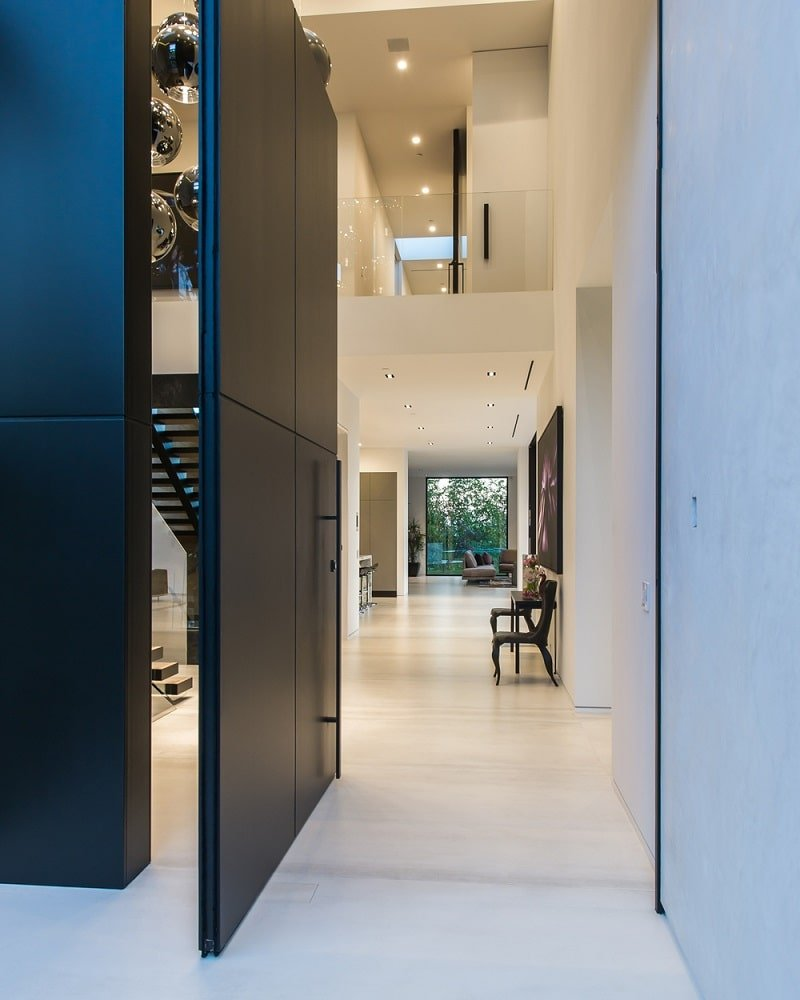 This is the pivot main door of the house with a black tone that makes it stand out against the bright white walls of the foyer. Image courtesy of Toptenrealestatedeals.com.