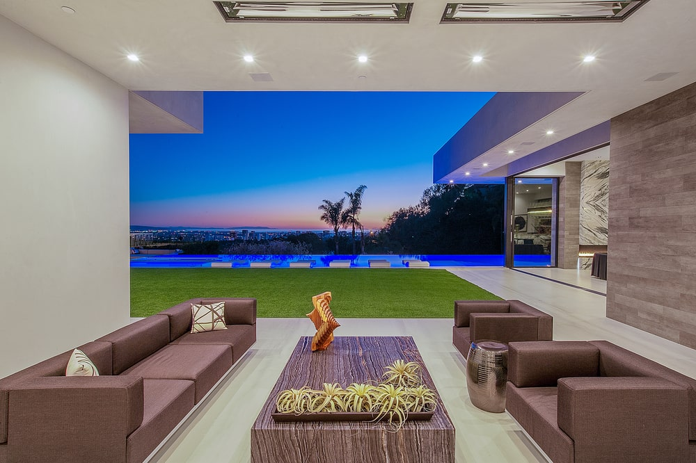 This is a look at the covered patio with a set of sectional sofas and armchairs paired with a large coffee table. These are complemented by the open wall that offeres a view of the backyard swimming pool. Image courtesy of Toptenrealestatedeals.com.