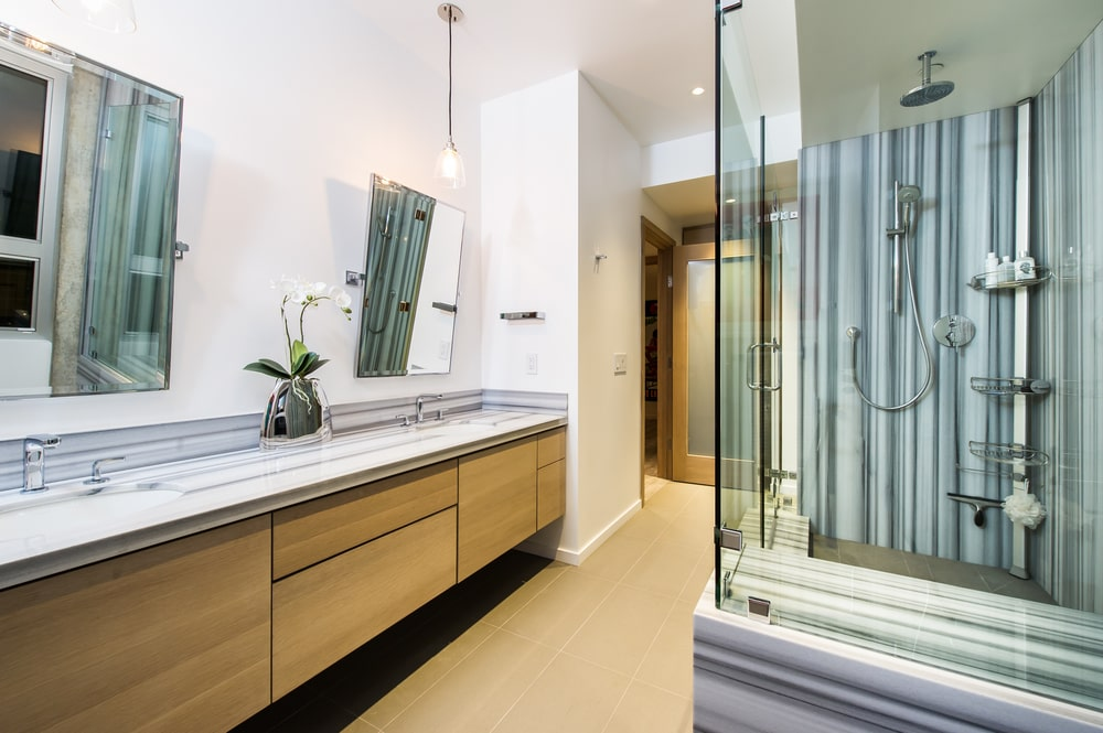The bathroom has a glass-enclosed shower area across from the floating wooden vanity topped with a mirror and a pendant light. Image courtesy of Toptenrealestatedeals.com.