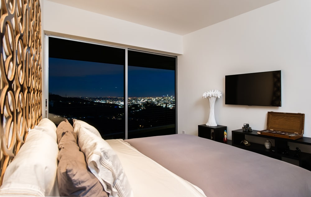 The bedroom has a small entertainment cabinet across from the bed. This is then topped with a wall-mounted TV and a large glass wall on the side. Image courtesy of Toptenrealestatedeals.com.