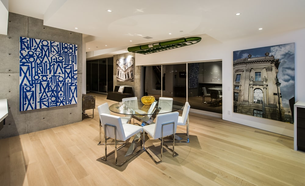 This angle of the dining area shows the round glass-top dining table surrounded by white modern chairs complemented by the light hardwood flooring and balcony glass doors. Image courtesy of Toptenrealestatedeals.com.