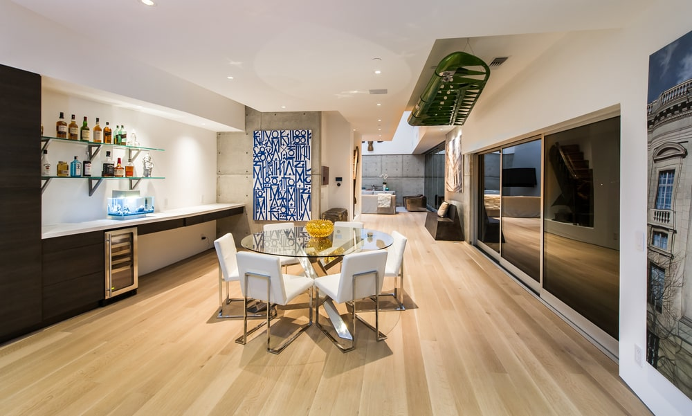 This other look at the dining area shows the large wall-mounted painting on the wall next to the kitchen along with a sculpture mounted on the ceiling. Image courtesy of Toptenrealestatedeals.com.