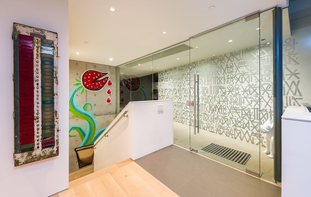 Upon entry of the house, you are welcomed by this foyer with glass walls, glass door and staircase adorned with a large and colorful mural. Image courtesy of Toptenrealestatedeals.com.