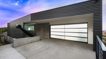This is the front view of the Industrial-style house with a bright garage door on the right, the main entrance on the far left and the fire-spewing missile art installation in the middle. Image courtesy of Toptenrealestatedeals.com.