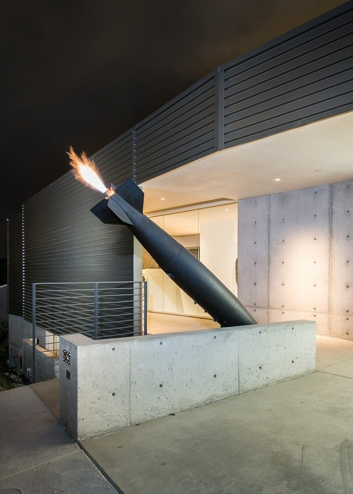 This is a closer look at the main entrance of the Industrial-style home that is adorned with a fire-spewing artwork of a missile. Image courtesy of Toptenrealestatedeals.com.