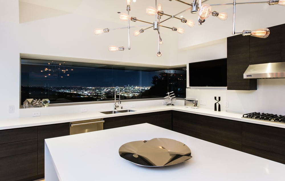 This is the kitchen with bright white tones on its walls, countertops and ceiling that has a modern chandelier over the kitchen island. Image courtesy of Toptenrealestatedeals.com.
