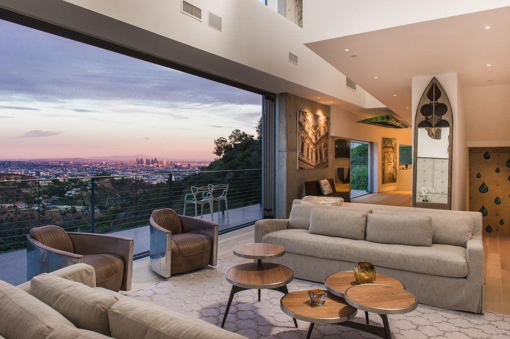This is the living room with a couple of light gray sofas flanking the coffee table with a wide open wall leading to the balcony with a sweeping view of the city below. Image courtesy of Toptenrealestatedeals.com.