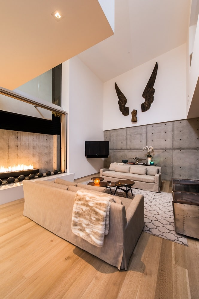 This different view of the living room showcases the large modern fireplace across from the coffee table. Image courtesy of Toptenrealestatedeals.com.