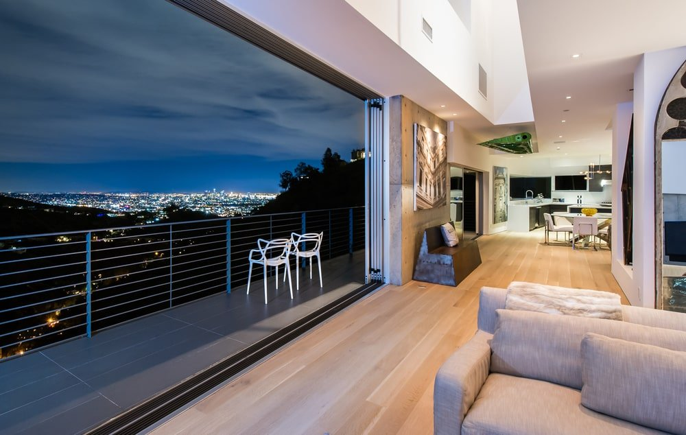 This angle of the large living room shows the set of balcony doors that disappear into the wall enabling the seamless transition of the living room to the balcony. Image courtesy of Toptenrealestatedeals.com.