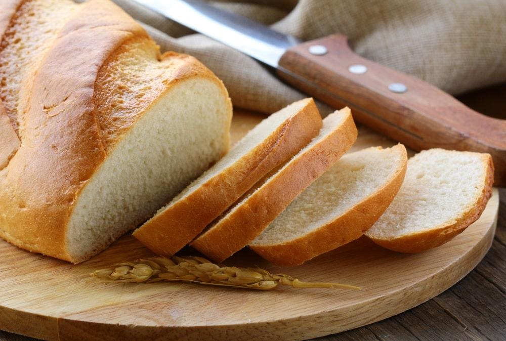 Sliced white sandwich bread on a wooden board.