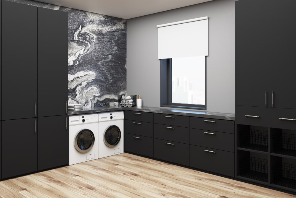 This is a laundry room installed with black built-in cabinetry to match the black marble wall.