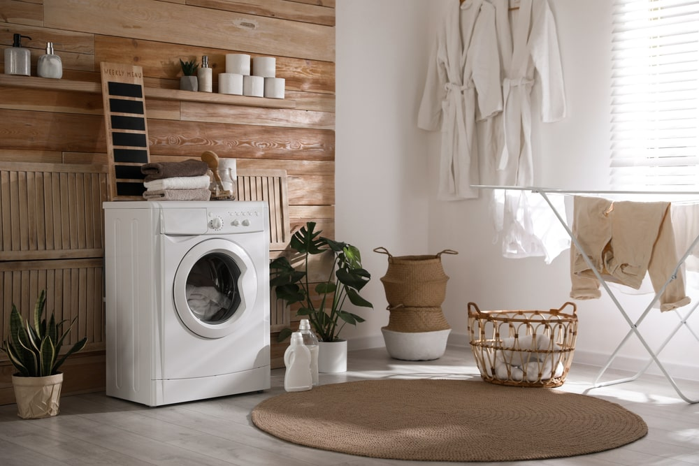 This laundry room has a white machine complemented by the wood-paneled wall and the potted plants.