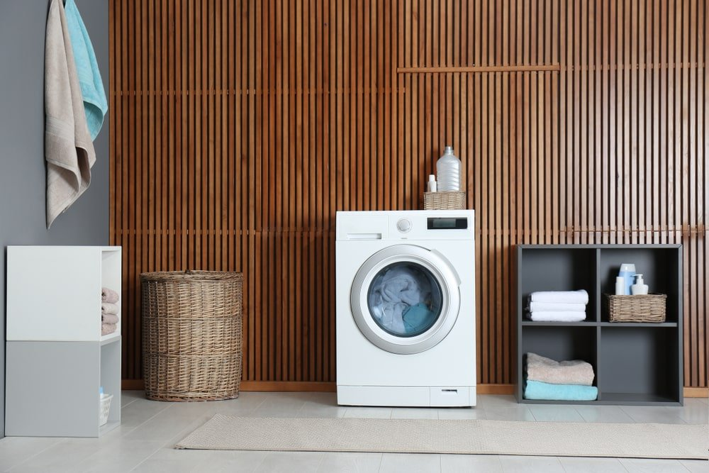 This laundry room has a white machine that stands out against the large wall of dark wood slats.