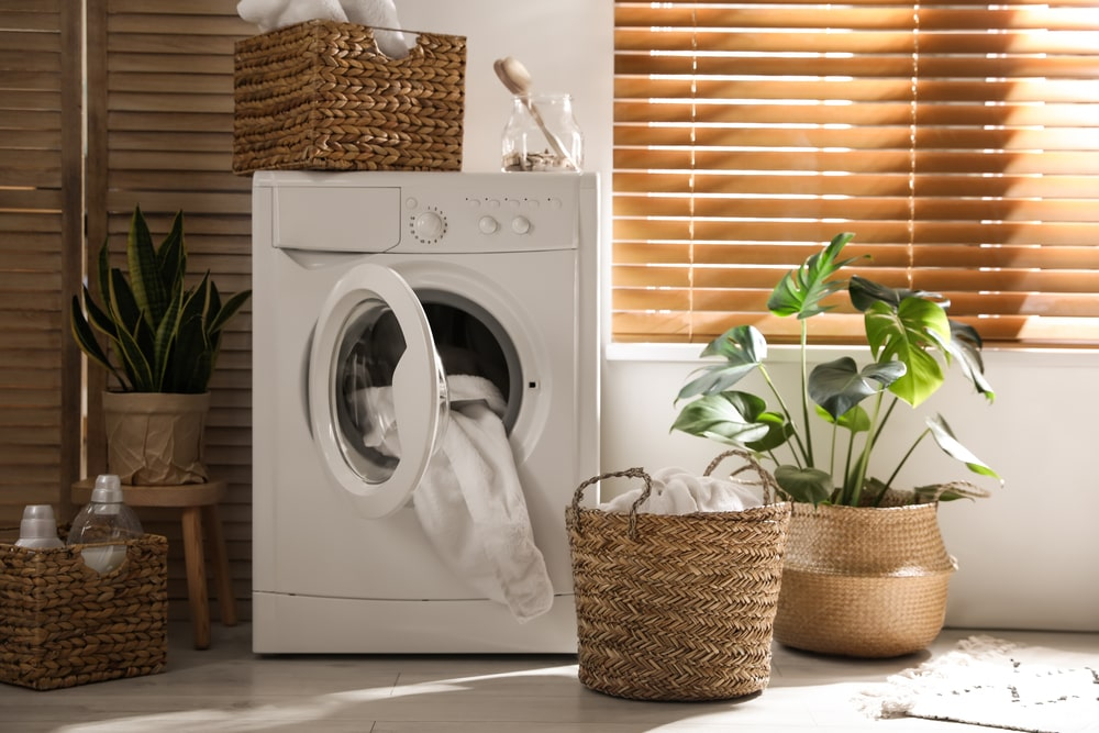 The white machine of this laundry room is complemented by the various woven wicker baskets and potted plants.