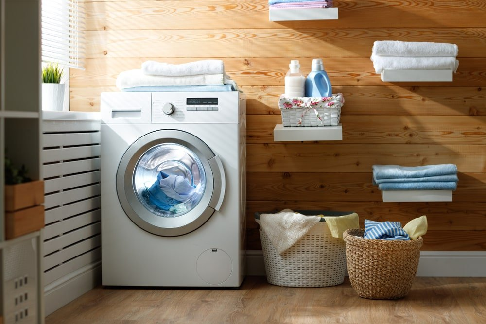 This is a laundry room with rustic wood-paneled walls adorned with floating shelves.